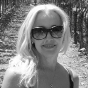 Picture of Mosaic Salon Owner Jeanna Johnson, standing in a vineyard.